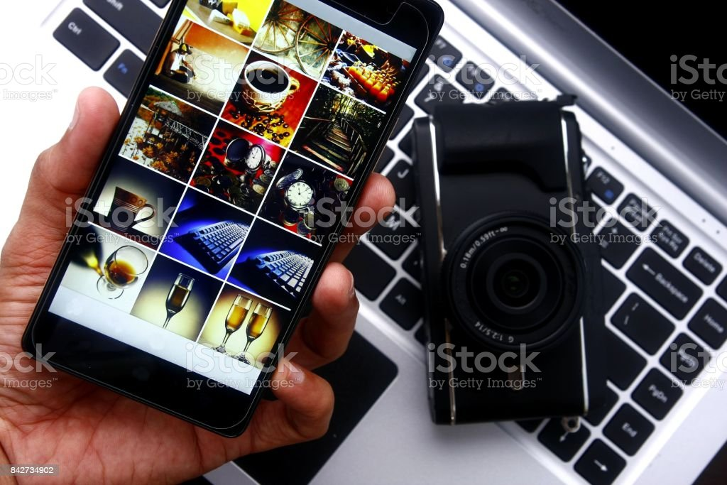 Hand holding a smartphone over a digital mirrorless camera and laptop computer stock photo