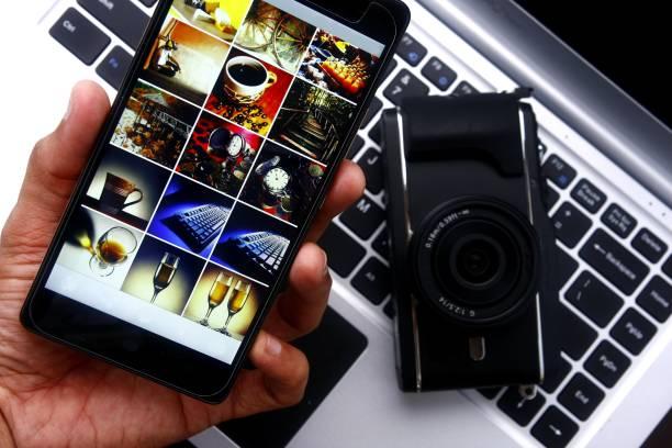 hand mit einem smartphone über einen digitalen spiegellose kamera und laptop-computer - tastatur bilder stock-fotos und bilder