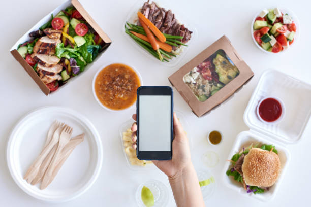 hand holding a smartphone over a table of various takeout options - food delivery стоковые фото и изображения