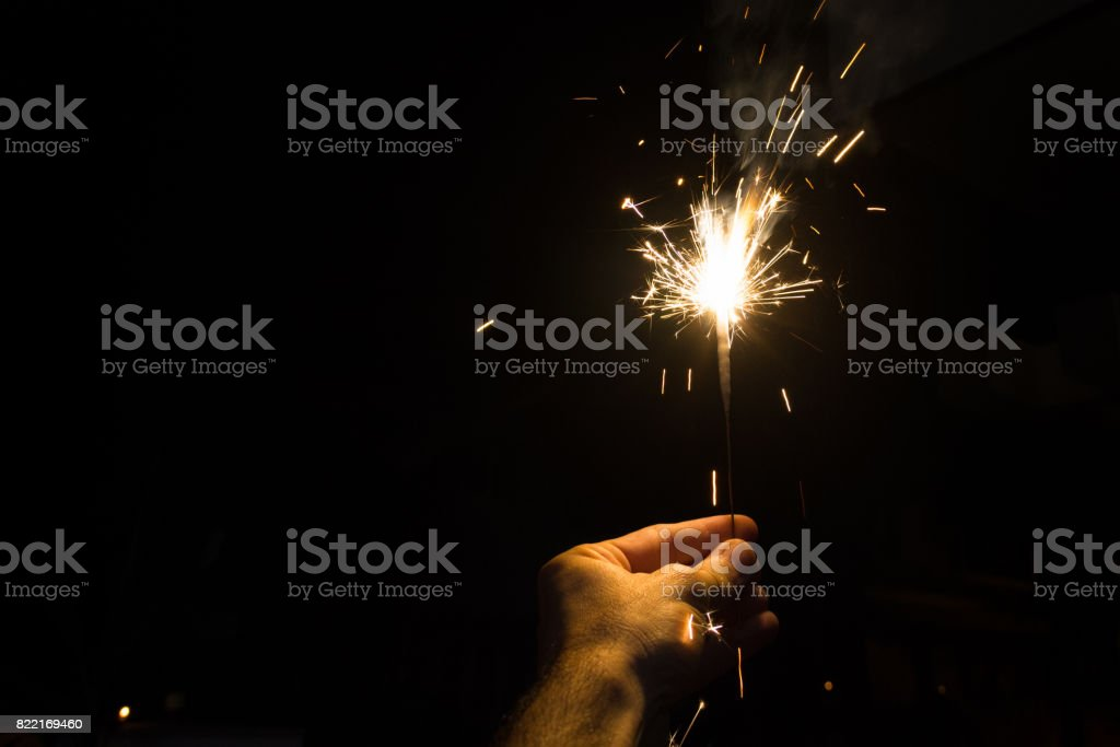 Hand holding a sparkler at night stock photo