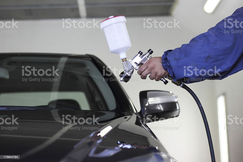 Hand holding a spray paint gun pointed at a black car stock photo