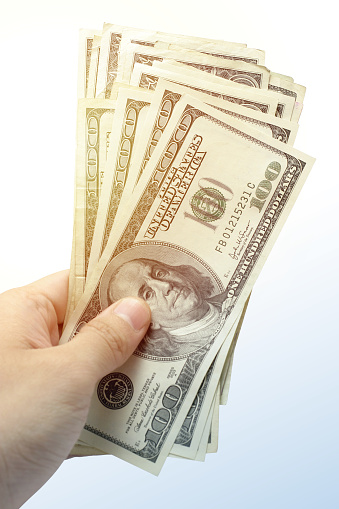 istock Hand Holding a Stack of US Hundred Dollar Bills Cash 1125517611