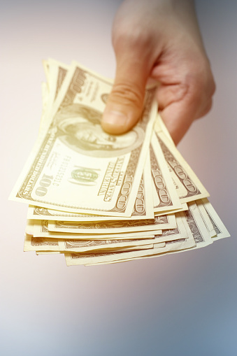 istock Hand Holding a Stack of US Hundred Dollar Bills Cash 1125517619