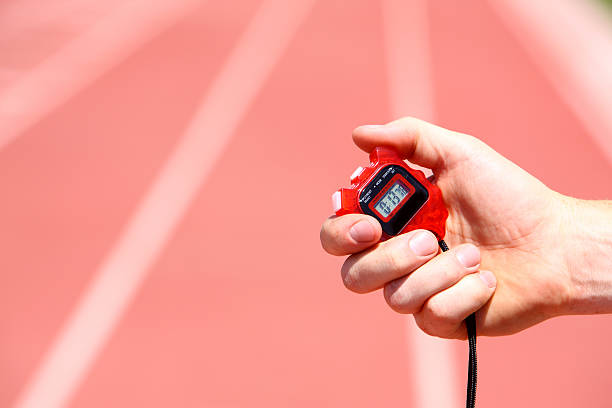 hand holding a stopwatch on a track - stopwatch stockfoto's en -beelden