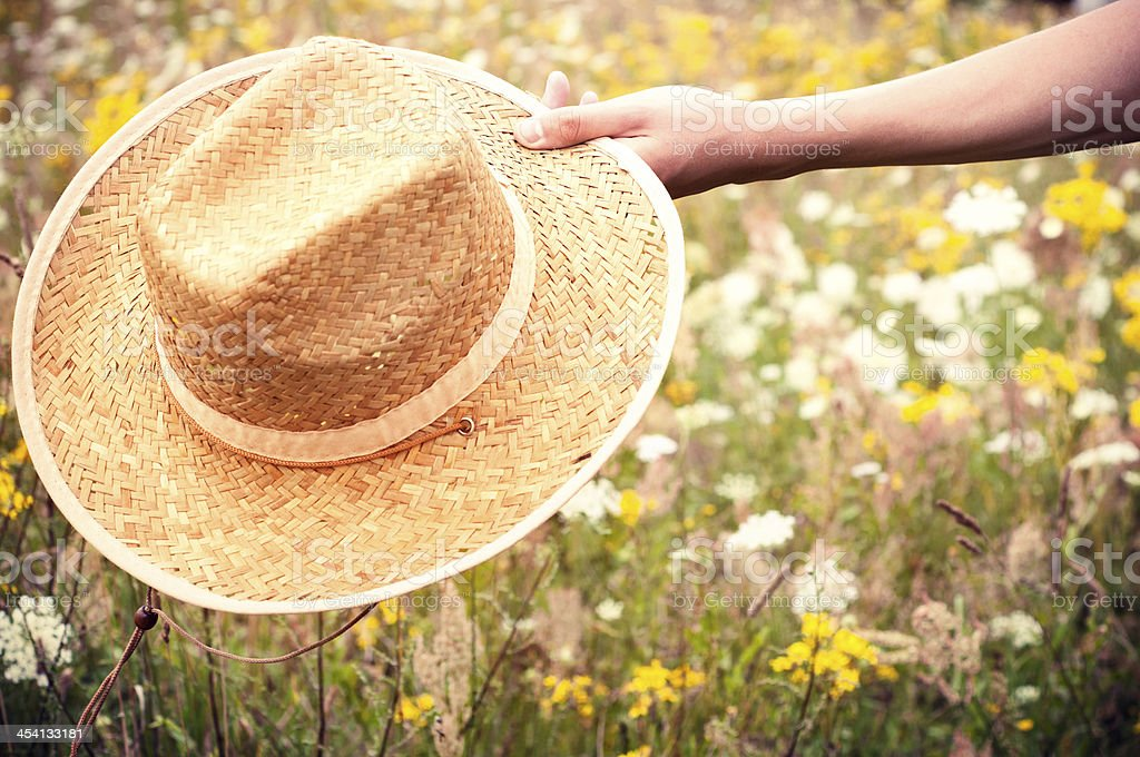 Hand holding a straw hat stock photo
