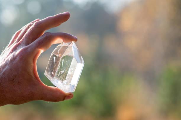 Eine Hand hält einen transparenter Kristall Quarz Edelstein – Foto