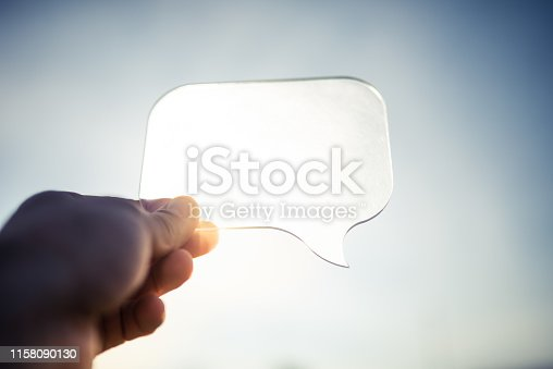 Hand holding a transparent speech bubble over the sunny sky