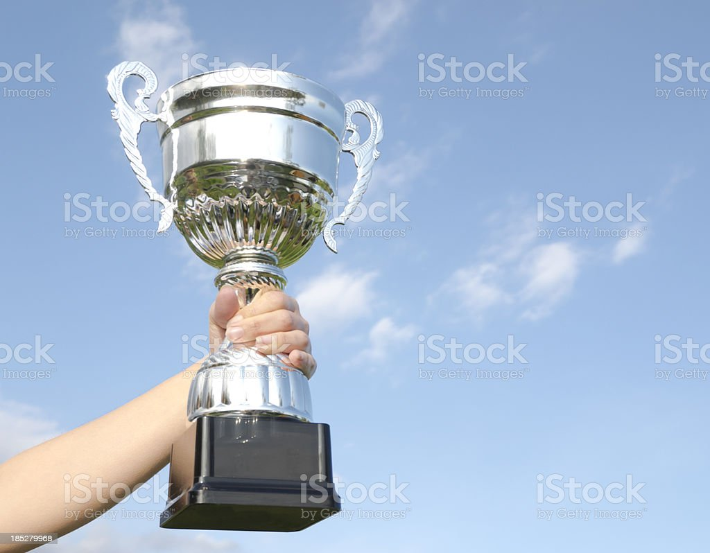Hand holding a trophy with a blue sky on the background royalty-free stock photo