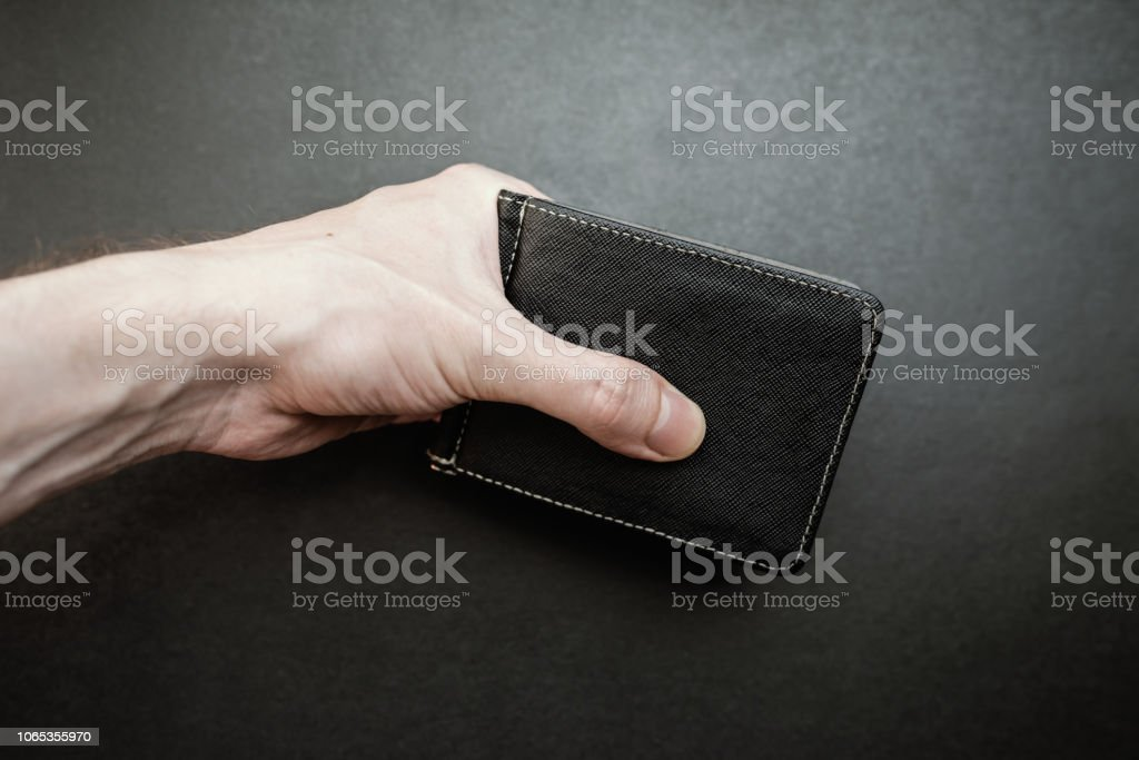 Hand holding a wallet. Selective focus with shallow depth of field.
