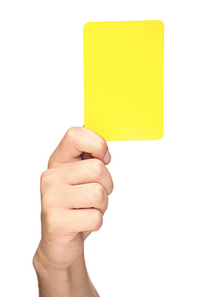hand holding a yellow card - judge sports official stock photos and pictures