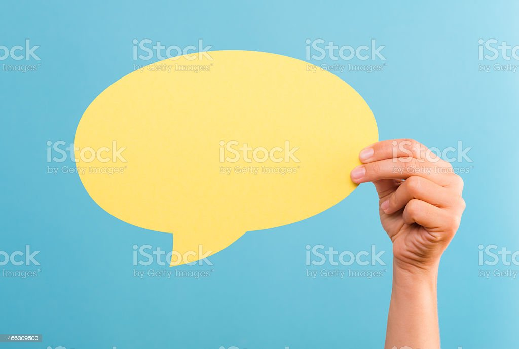 Hand holding a yellow text bubble over a blue background stock photo