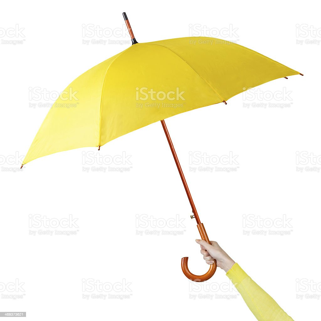 Hand holding a yellow umbrella stock photo