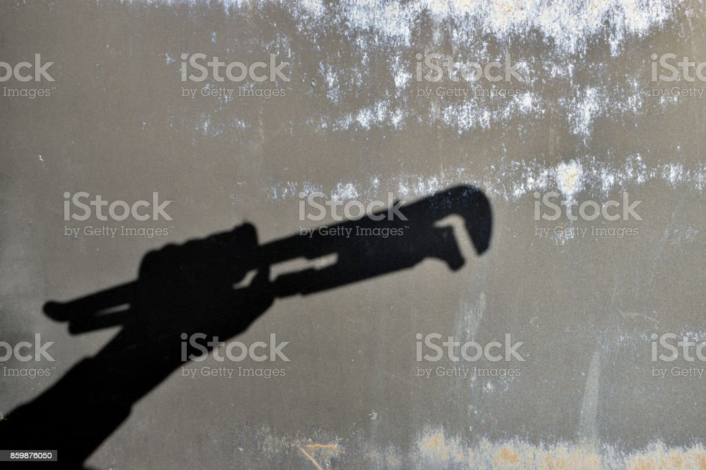 Hand holding adjustable spanner; wrench. repair - shadow the wall stock photo