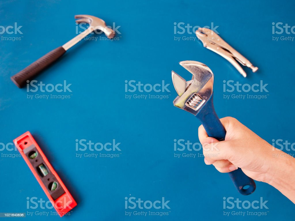 Hand holding adjustable wrench, background is variety handy tools on...
