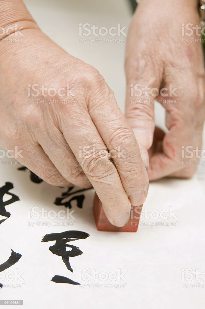 Hand holding agalmatolite stamp stock photo