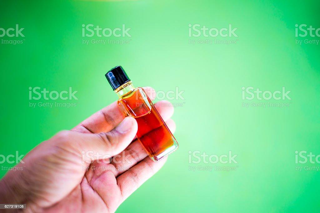 Hand holding agarwood oil fragrances in mini bottle stock photo