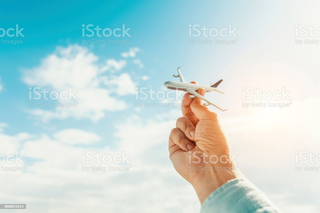 hand holding airplane model in front of cloudy blue sky background. air transportation concept. stock photo
