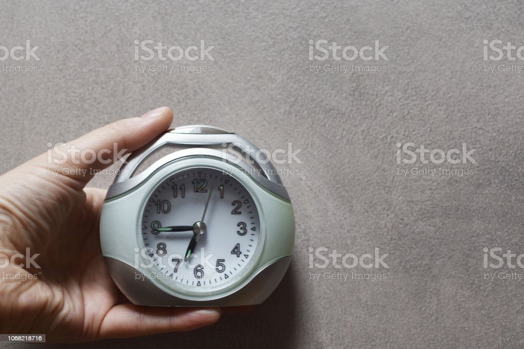 Hand holding alarm clock showing quarter to seven on grey grunge...