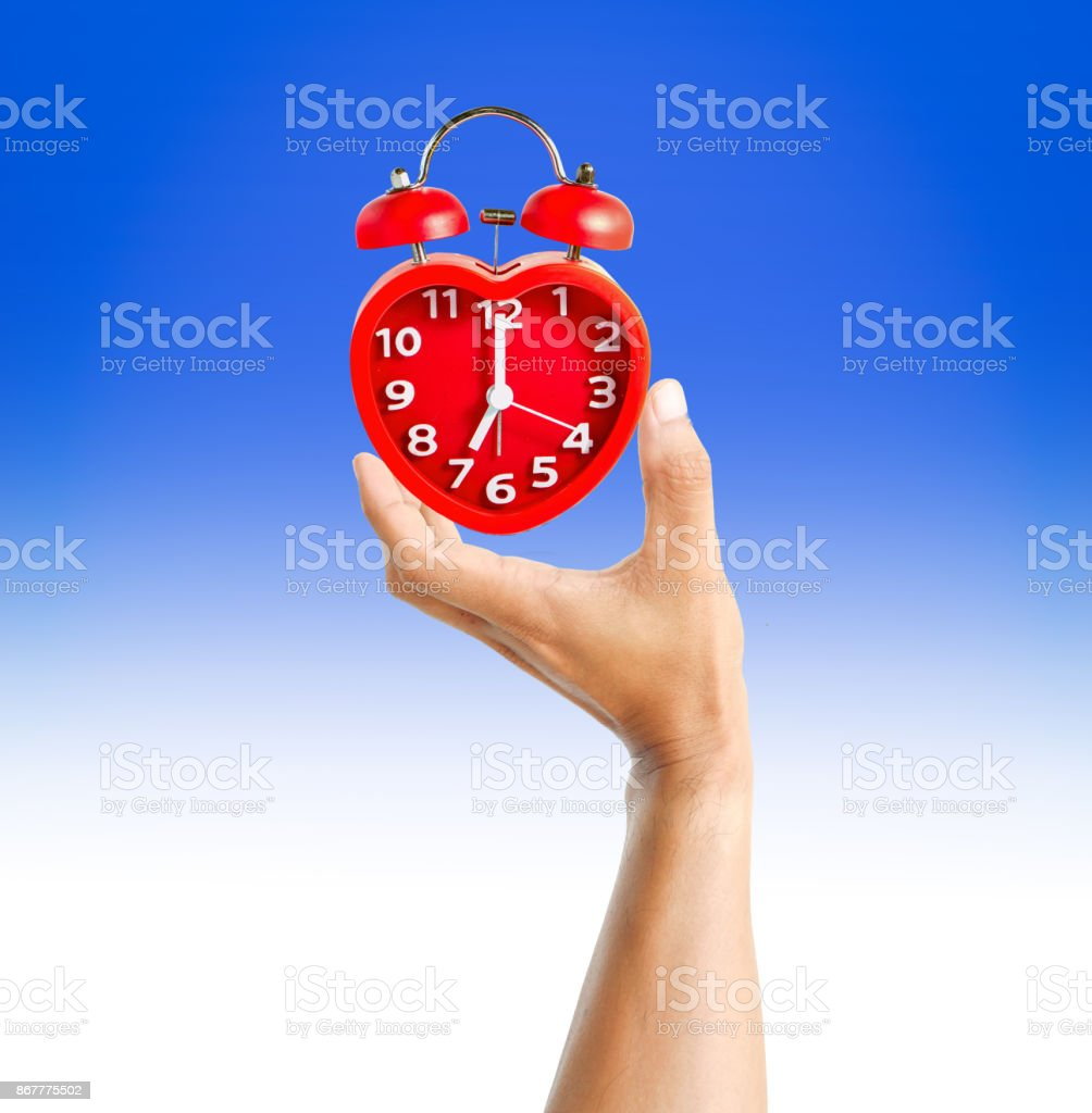 Hand holding alarm red clock stock photo