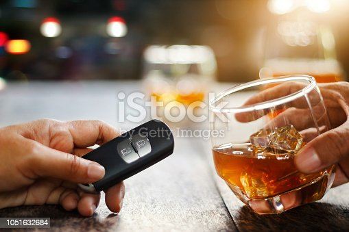 istock Hand holding alcoholic drink, another hold car remote, Drunk driving concept. 1051632684