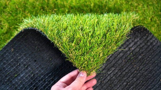 Hand holding an artificial grass roll. Greenering with an artificial turf. Hand holding an artificial grass roll. Greenering with an artificial turf. imitation stock pictures, royalty-free photos & images