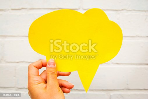 465462550istockphoto Hand holding an empty yellow hand-cuted paper speech bubble on white textured brick wall background. Isolated. 1034461990