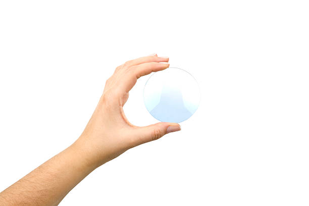 Hand holding an eyeglass lens without the glasses on white stock photo