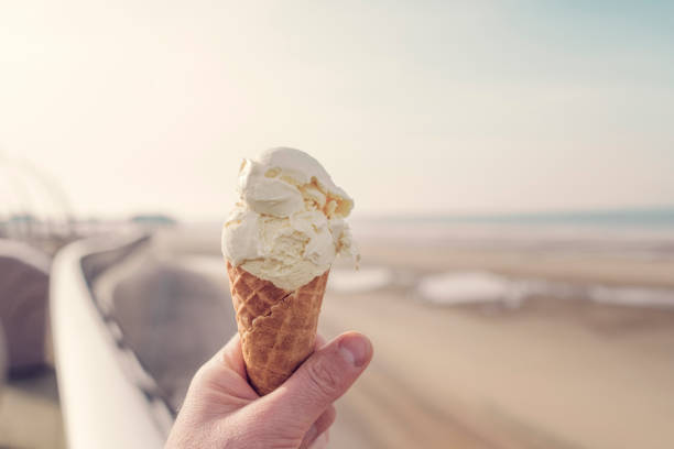 hand holding an ice cream cone at blackpool seafront. - ice cream cone stock photos and pictures