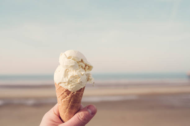 hand holding an ice cream cone overlooking the beach at blackpool at low tide on a sunny day. - ice cream cone stock photos and pictures