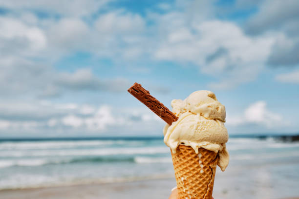 pov hand holding an ice cream over fistral beach, newquay, cornwall on a cloudy/sunny autumn day. - ice cream cone stock pictures, royalty-free photos & images