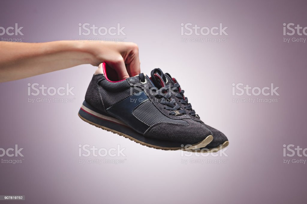 Hand Holding An Old Dirty Sneaker Shoe stock photo