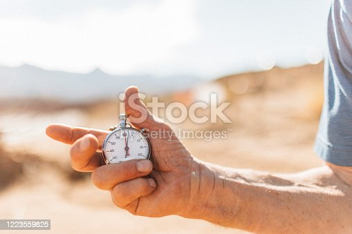 A hand holding an old fashioned stopwatch in the out of doors