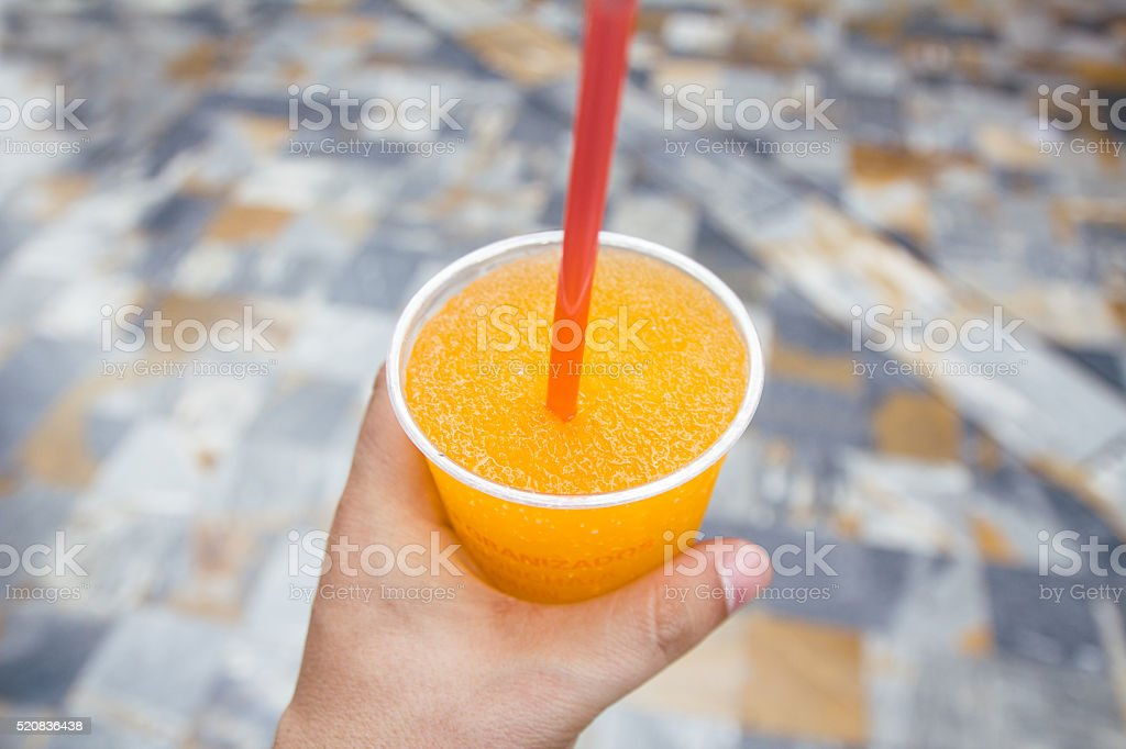 Hand holding an orange slush in a street stock photo