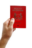 Close-up on a man's hand holding an Singaporean passport against a white background.