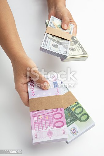 Hand holding and giving Euro and dollars banknotes