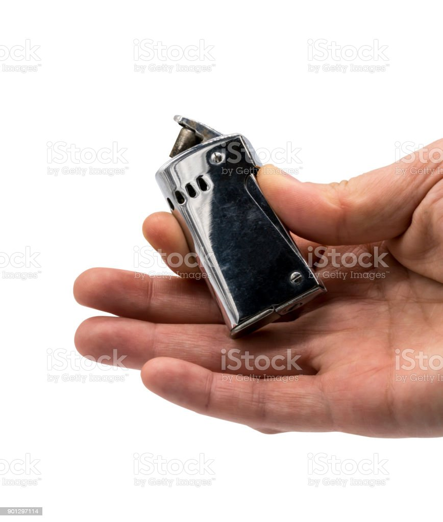 Hand holding and pressing vintage retro silver lighter isolated on white background stock photo