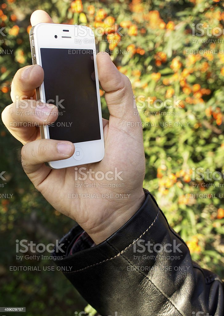 Hand holding and touching iPhone 4S stock photo