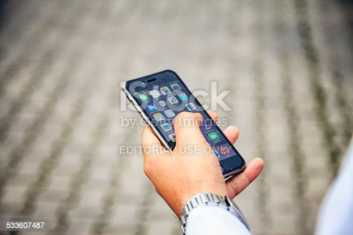 istock Hand holding and touching iPhone 6 533607487