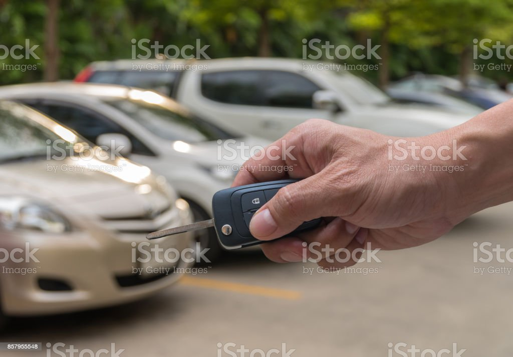 Hand holding and touching the keys over photo blurred of used car for open the door car, transportation and ownership concept stock photo