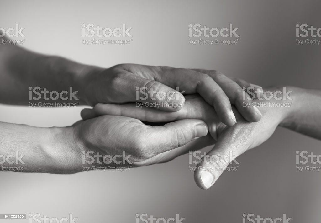 Hand holding another hand stock photo