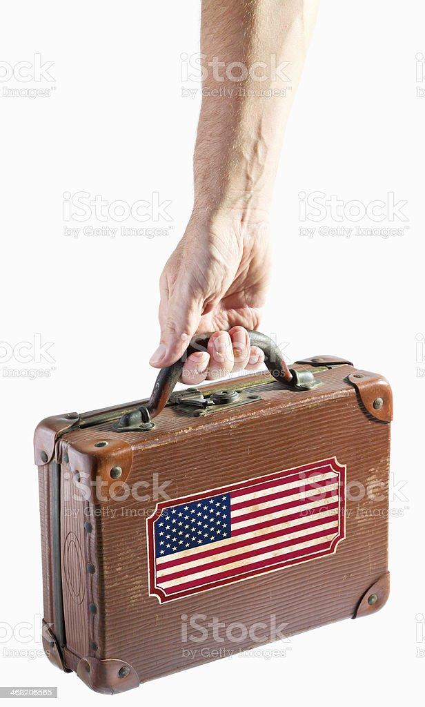 Mão segurando antigo mala de viagem de couro com bandeira dos Estados Unidos - foto de acervo