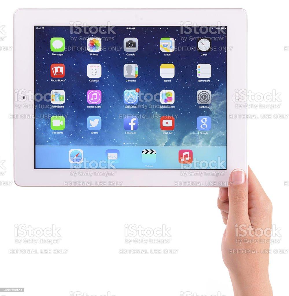 Hand holding Apple iPad 3 displaying iOS 7 home screen stock photo