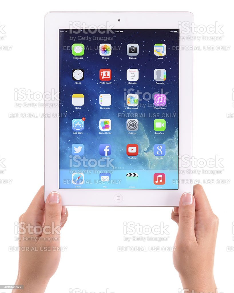 Hand holding Apple iPad 3 displaying new iOS 7 screen stock photo