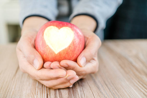 hand holding apple pie with heart shape, concept of love stock photo