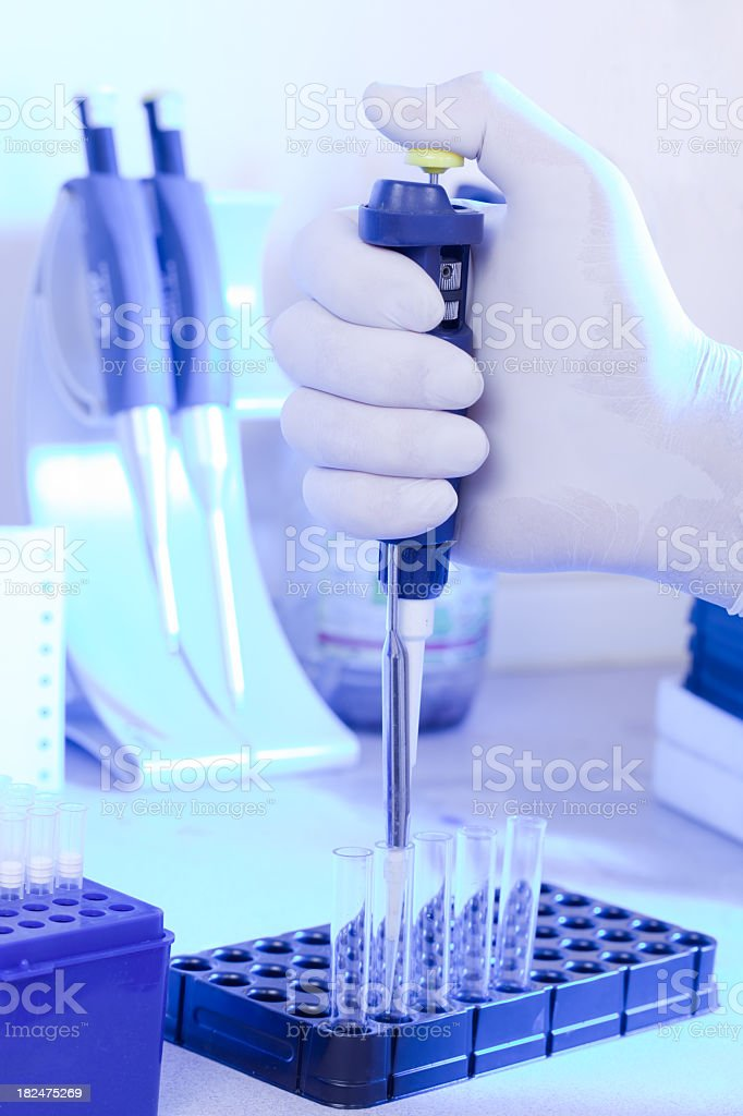 Hand holding automatic pipette on lab setting royalty-free stock photo