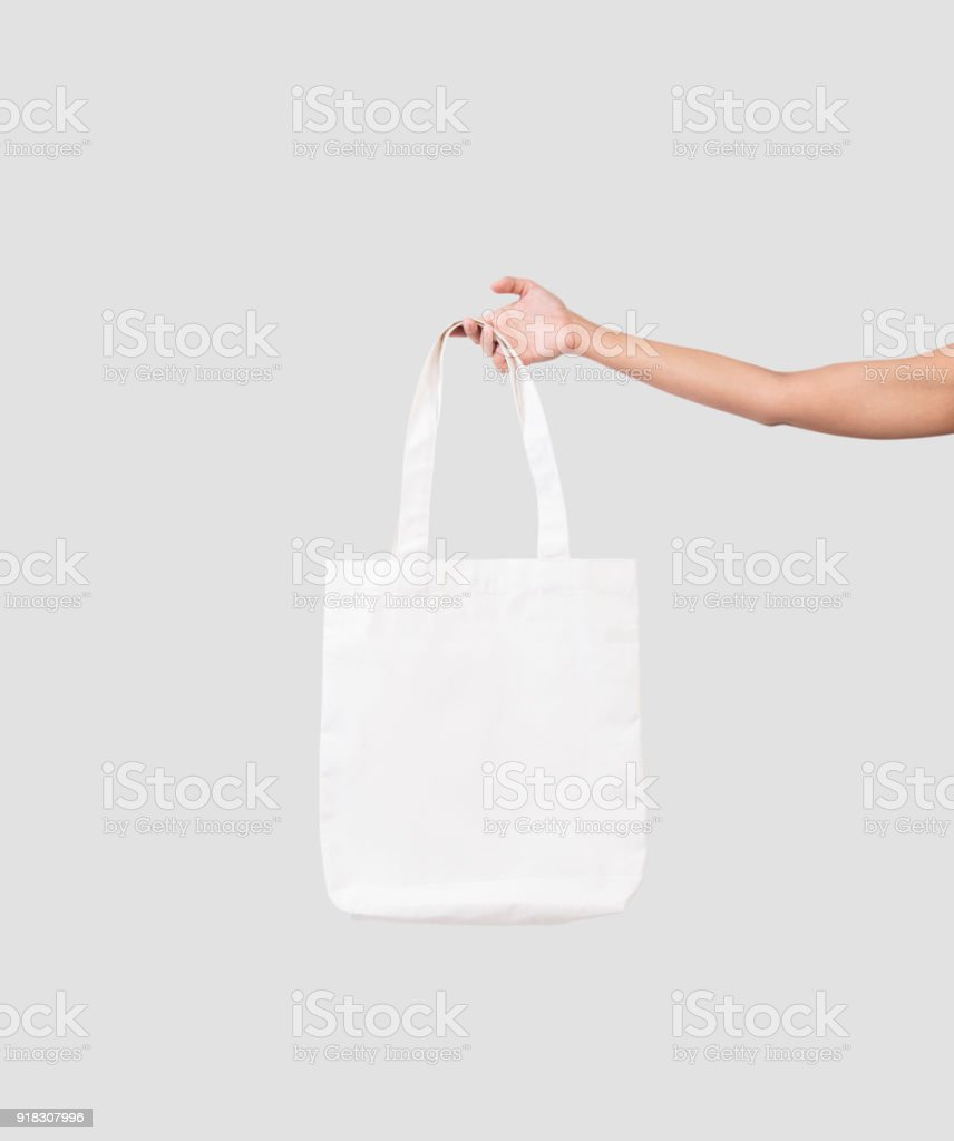 hand holding bag canvas fabric for mockup blank template isolated on gray background. stock photo