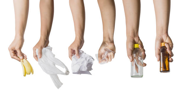 main tenant la peau de banane, sac en plastique blanc, papier froissé, verre en plastique et bouteilles - recyclage main photos et images de collection