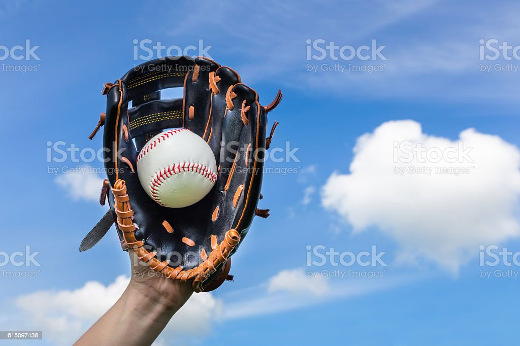 Hand holding baseball in glove with blue sky stock photo