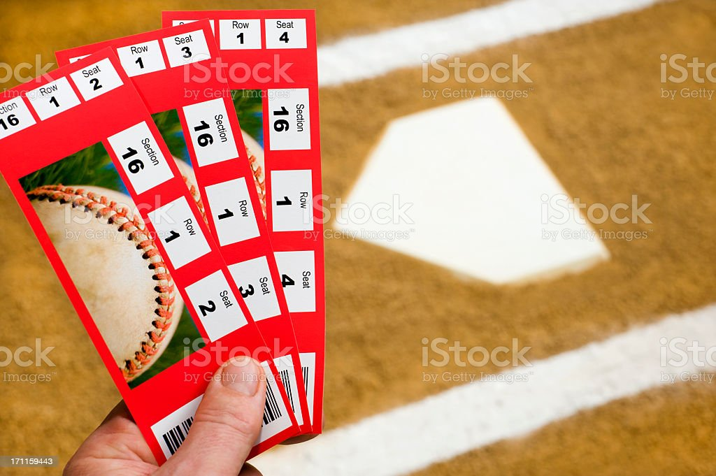 A Hand holding three baseball ticket stubs at home plate with the...
