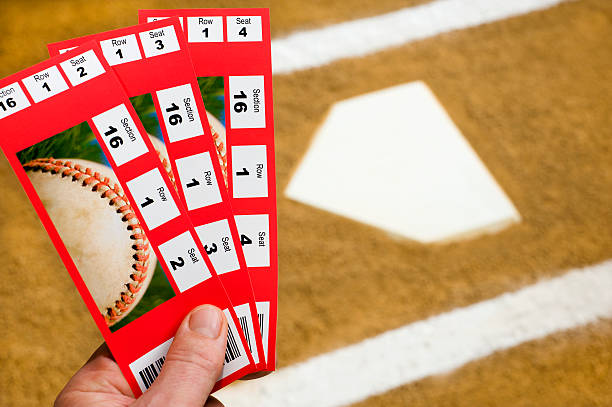 hand holding baseball tickets at home plate - ticket stock photos and pictures